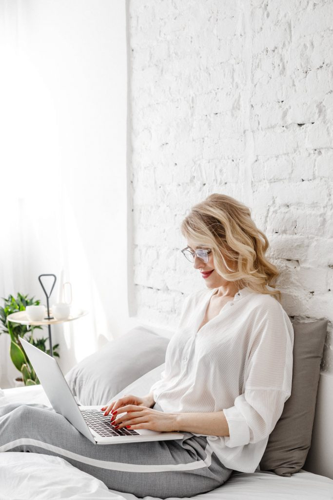 Authentic Pricing woman leaning against wall with laptop
